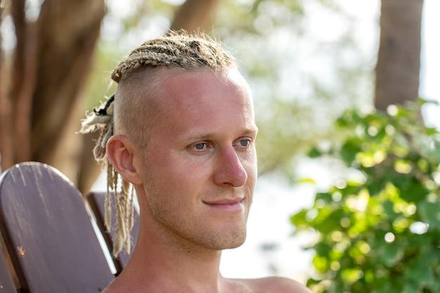 Portrait d'un jeune homme avec des dreadlocks sur la tête dans la nature. heureux bel homme avec des dreadlocks sur la plage tropicale, gros plan