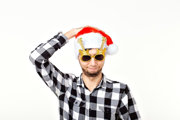 Portrait d'un jeune homme drôle en chapeau de père noël et barbe sur un espace blanc. noël.