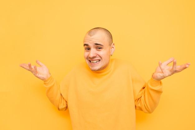 Portrait d'un jeune homme drôle se brise les bras et se penche sur l'appareil photo