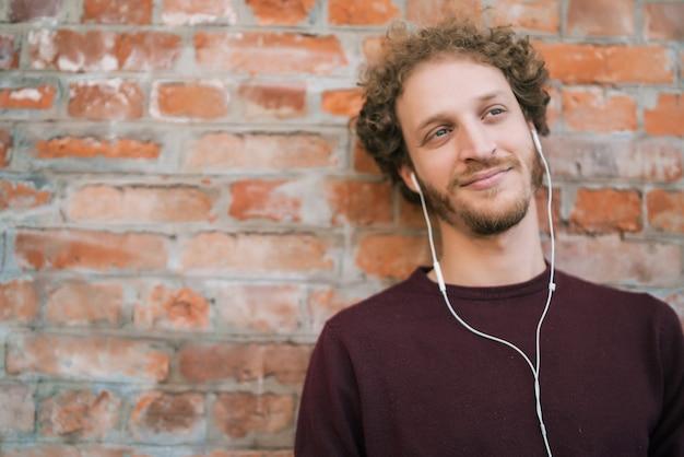 Portrait de jeune homme écoutant de la musique avec des écouteurs contre le mur de briques. concept urbain.