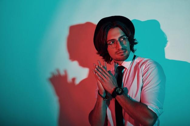 Portrait de jeune homme élégant au chapeau et avec des lunettes qui se dressent dans les néons du studio.