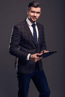Portrait d'un jeune homme élégant brutal avec tablette
