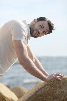 Portrait de jeune homme élégant près de la mer vêtu d'un polo blanc