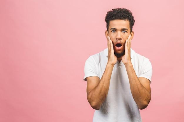Portrait de jeune homme étonné avec une coiffure afro en t-shir blanc, regardant à huis clos avec la bouche ouverte et l'expression choquée.