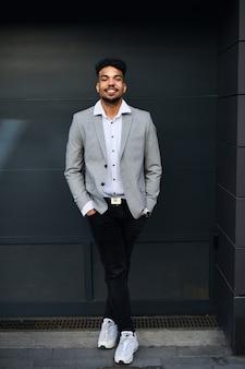 Un portrait de jeune homme étudiant debout à l'extérieur en ville sur fond noir