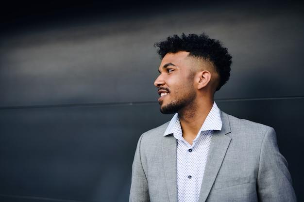 Un portrait de jeune homme étudiant debout à l'extérieur de la ville sur fond noir.