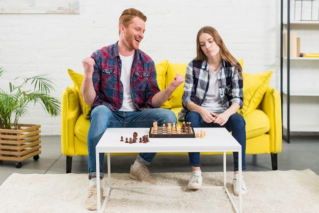 Portrait d'un jeune homme excité assis avec sa petite amie triste jouant aux échecs