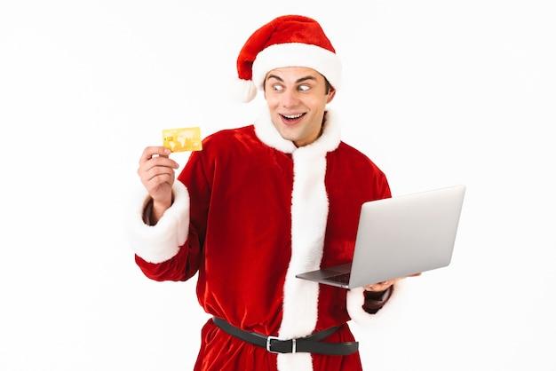 Portrait d'un jeune homme excité habillé en costume de père noël debout isolé sur un espace blanc, tenant un ordinateur portable