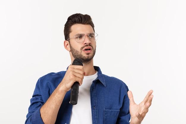 Portrait d'un jeune homme excité en t-shirt isolé sur fond gris, chantant.