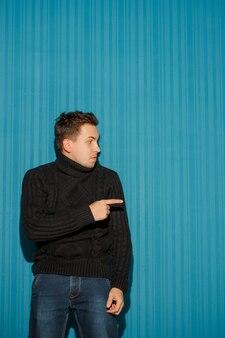 Portrait de jeune homme avec une expression faciale grave montrant vers la droite sur fond bleu