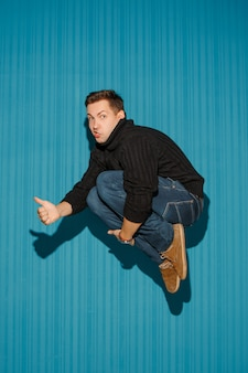 Portrait de jeune homme avec une expression faciale sérieuse sautant