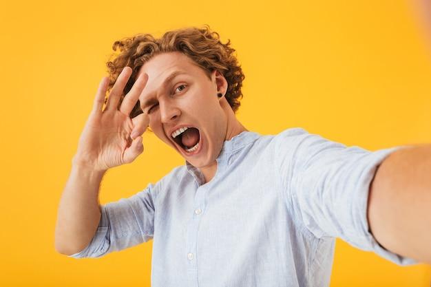 Portrait de jeune homme extatique prenant selfie photo et montrant le signe ok avec les doigts, isolé sur fond jaune