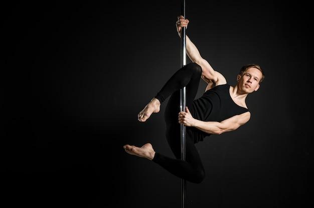 Portrait de jeune homme faisant une pole dance
