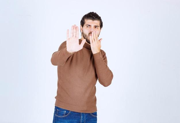 Portrait d'un jeune homme faisant s'arrêter avec ses mains. photo de haute qualité