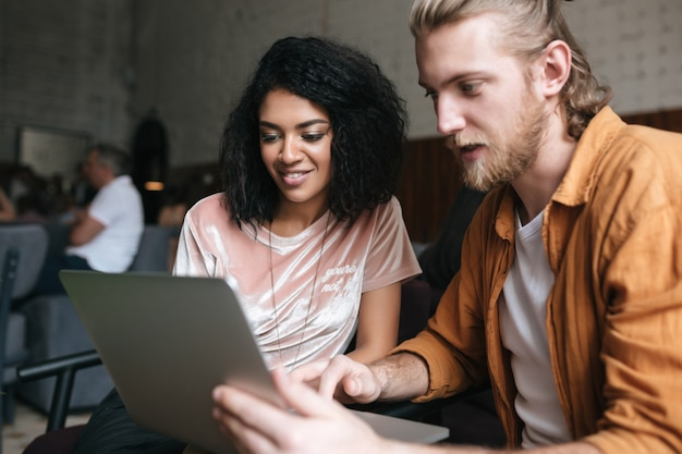 Portrait de jeune homme et femme assis dans un restaurant et travaillant sur ordinateur portable