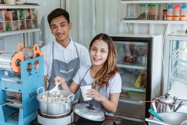 Portrait jeune homme et femme vendant le plat de boulettes de viande dans sa petite boutique
