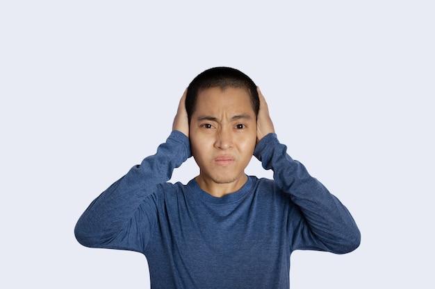 Portrait de jeune homme fermant les oreilles à la main fond isolé.
