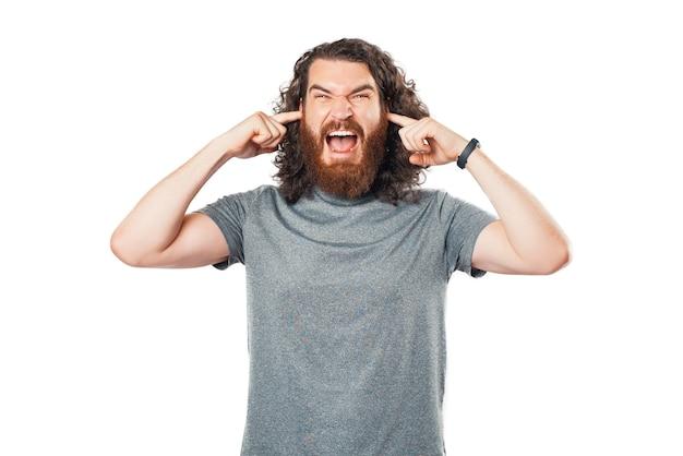 Portrait de jeune homme fermer les oreilles avec les doigts sur fond blanc