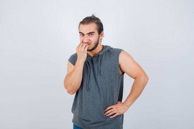 Portrait de jeune homme fit mordre les ongles en sweat à capuche sans manches et à la vue de face stressée