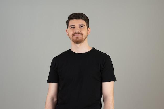 Portrait de jeune homme sur fond gris.