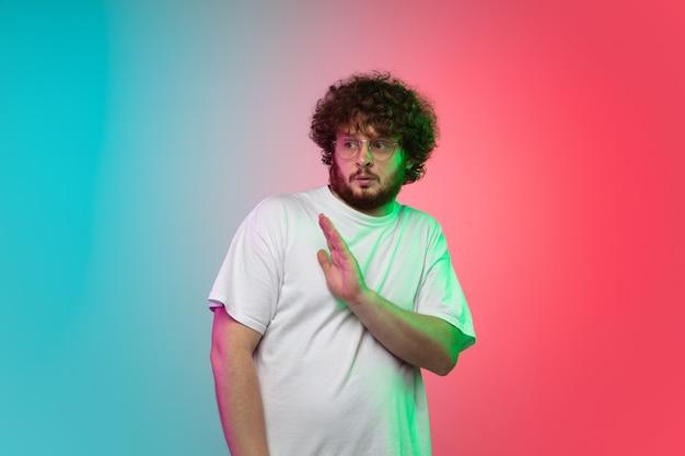 Portrait de jeune homme sur fond de studio dégradé en néon