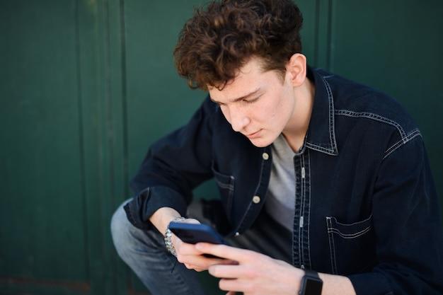 Portrait de jeune homme sur fond vert à l'extérieur, à l'aide de smartphone.