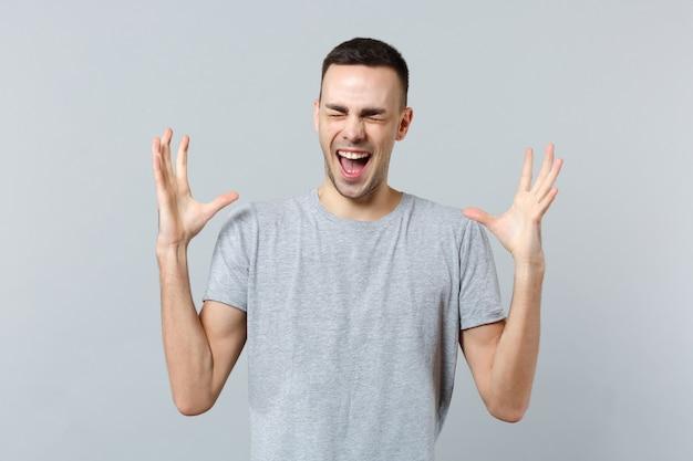 Portrait d'un jeune homme fou qui crie dans des vêtements décontractés, gardant les yeux fermés, écartant les mains