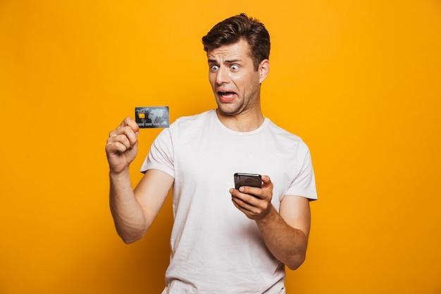 Portrait d'un jeune homme frustré tenant un téléphone mobile