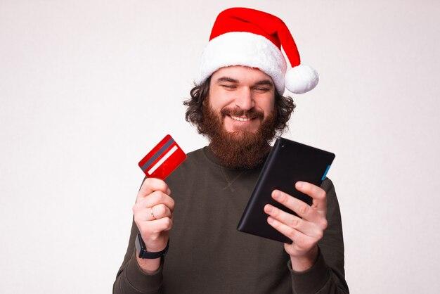 Portrait d'un jeune homme gai avec une barbe portant un chapeau de père noël et achetant en ligne avec une carte de crédit et une tablette