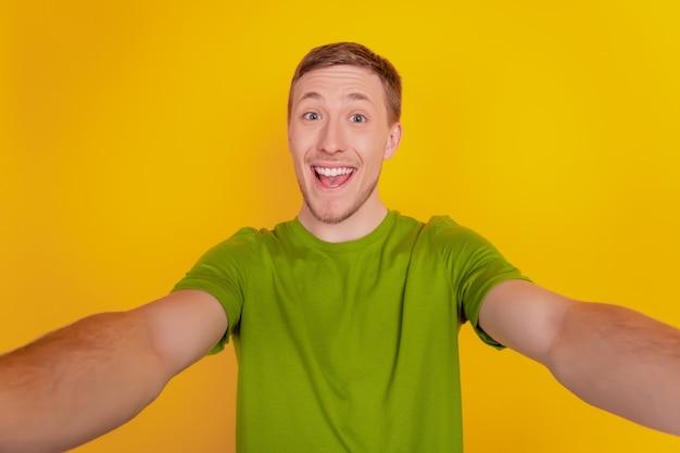 Portrait de jeune homme gai heureux sourire positif prenant un selfie isolé sur fond de couleur jaune