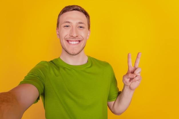 Portrait de jeune homme gai heureux sourire positif prenant un selfie montrer paix cool signe v isolé sur fond de couleur jaune