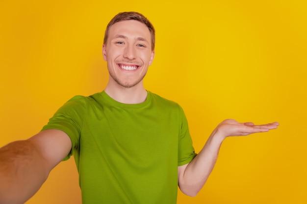 Portrait de jeune homme gai heureux sourire positif prenant un selfie show objet présent isolé sur fond de couleur jaune