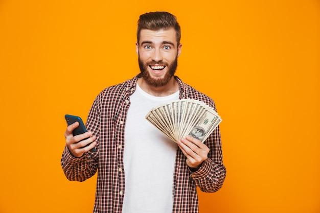 Portrait d'un jeune homme gai portant des vêtements décontractés tenant un téléphone mobile montrant des billets d'argent