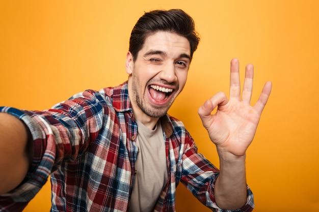 Portrait d'un jeune homme gai prenant un selfie