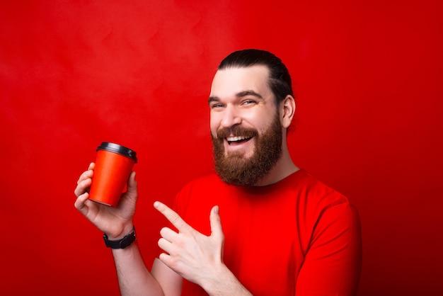 Portrait de jeune homme gai souriant et pointant sur la tasse de café pour aller sur le mur rouge