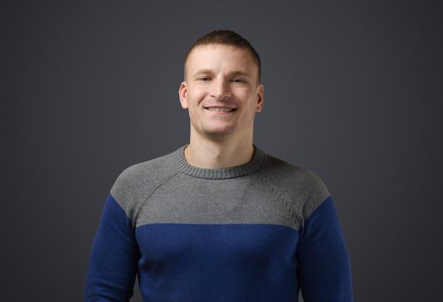 Portrait d'un jeune homme gay qui sourit. photo émotionnelle en studio sur une surface noire