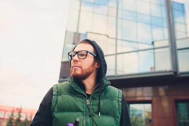 Portrait de jeune homme avec une grande barbe dans des verres vaping une cigarette électronique en face de l'arrière-plan urbain.