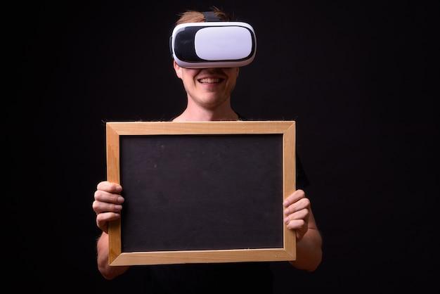Portrait de jeune homme heureux à l'aide d'un casque de réalité virtuelle et tenant le tableau noir
