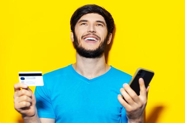 Portrait de jeune homme heureux à l'aide de smartphone et carte de crédit sur la couleur jaune