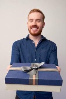 Portrait d'un jeune homme heureux donnant une boîte-cadeau bleu foncé avec un arc à la caméra