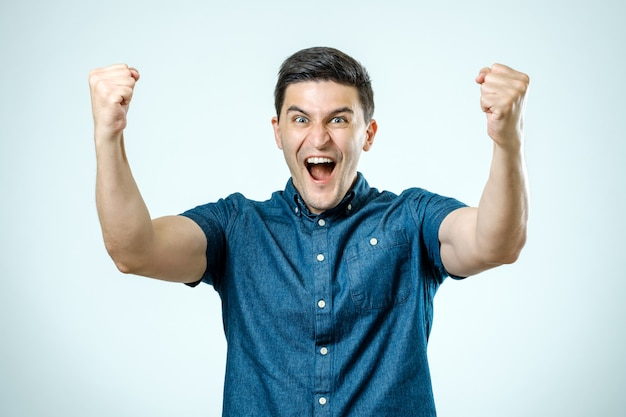 Portrait de jeune homme heureux, levant les mains