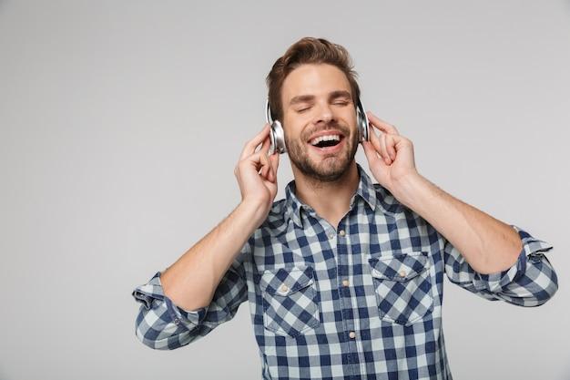 Portrait d'un jeune homme heureux portant une chemise à carreaux à l'aide d'un casque et souriant isolé sur un mur blanc