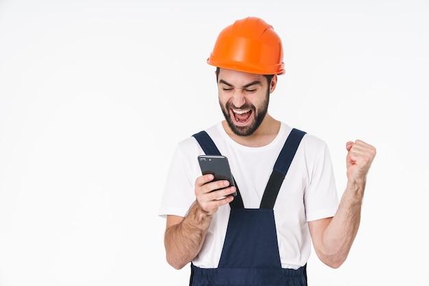 Portrait d'un jeune homme heureux et positif en casque posant isolé sur un mur blanc à l'aide d'un téléphone portable.