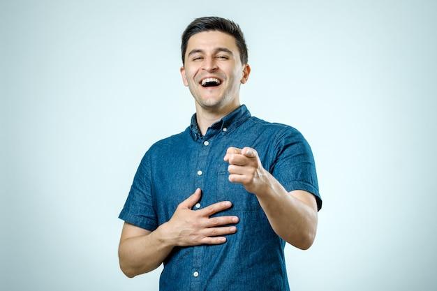 Portrait jeune homme heureux, riant, pointant du doigt quelqu'un