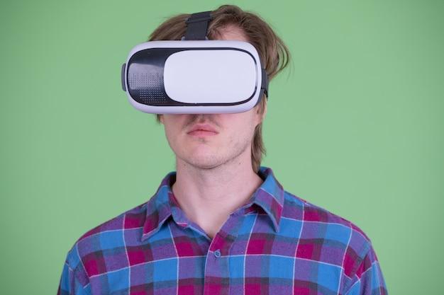 Portrait de jeune homme hipster scandinave beau contre chroma key ou mur vert