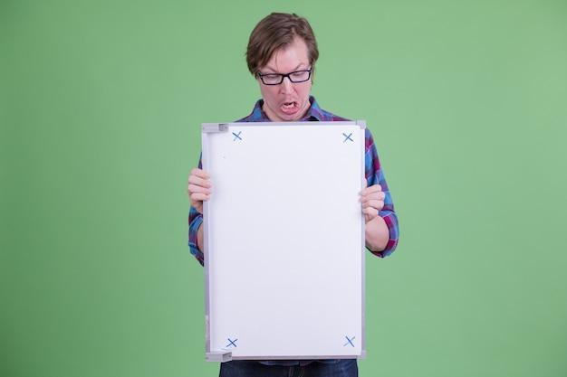 Portrait de jeune homme hipster scandinave beau avec des lunettes contre clé chroma ou mur vert