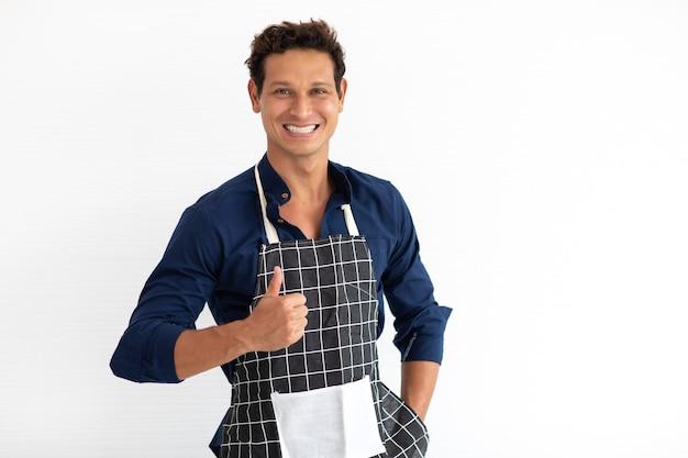 Portrait de jeune homme hispanique souriant en tablier regardant la caméra isolée sur fond blanc