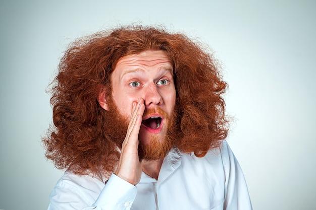 Portrait de jeune homme hurlant aux longs cheveux roux et expression faciale choquée sur fond gris