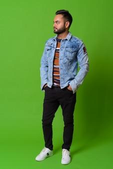 Portrait de jeune homme indien barbu sur vert