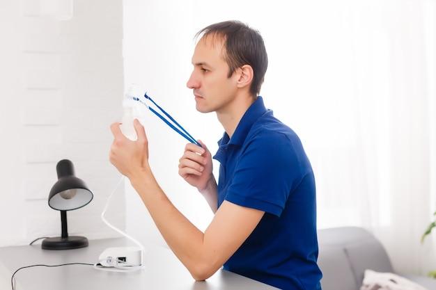 Portrait de jeune homme inhalant par masque d'inhalateur